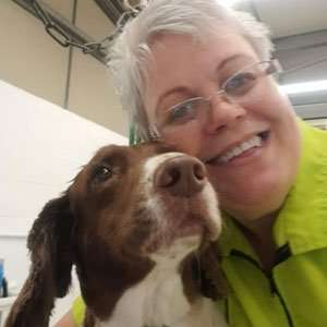 graduate from the Paw Pad Dog Grooming Academy with a brown and white dog